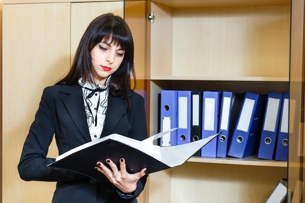 Belle jeune femme brune, lecture de documents au bureau. Photo Premium