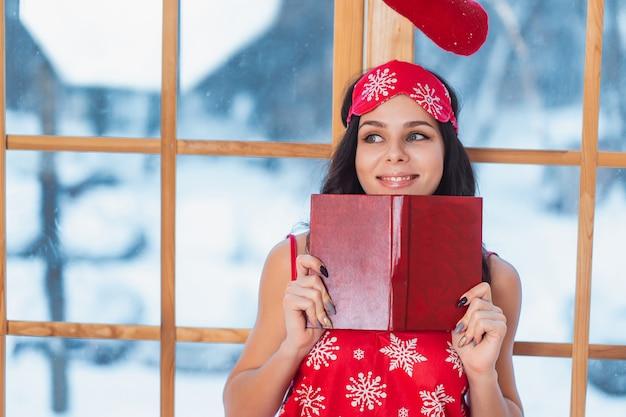 Belle Jeune Femme Brune En Pyjama Rouge Et Lecture Par La Fenêtre Photo gratuit