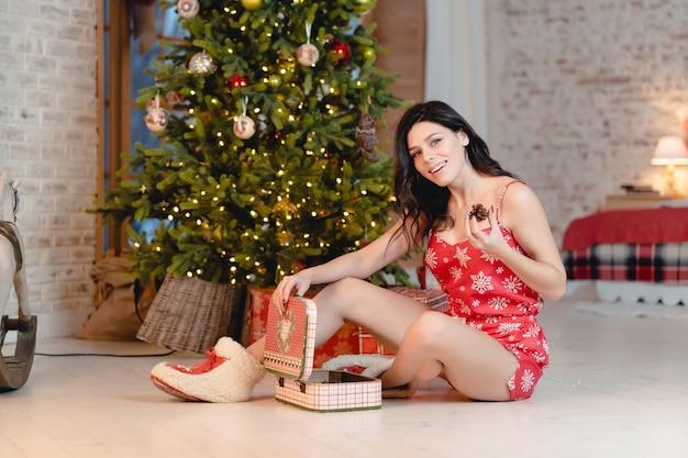 Belle Jeune Femme Avec Des Cadeaux Sur L'arbre De Noël Photo gratuit
