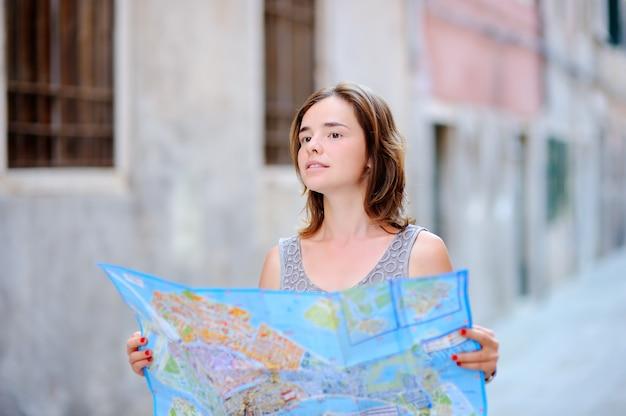 Belle jeune femme avec carte en papier debout dans la rue à venise, italie Photo Premium