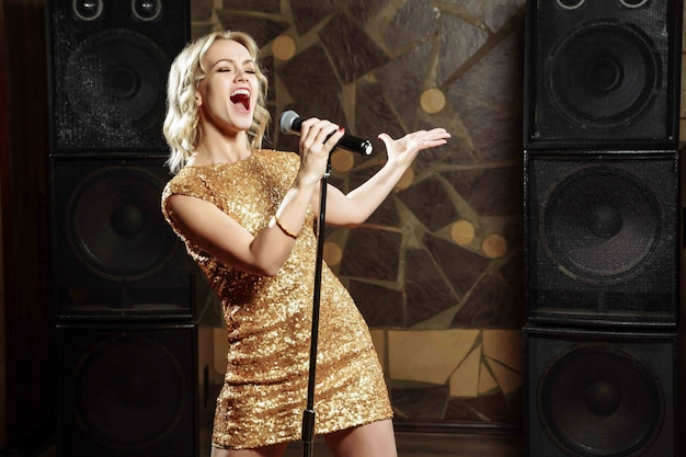 Belle jeune femme chantant avec le micro Photo Premium