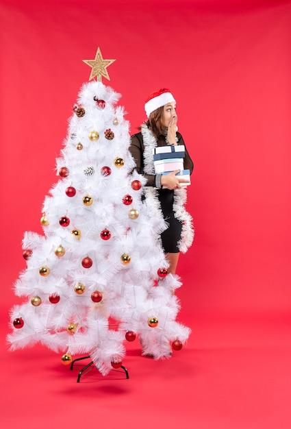 Belle Jeune Femme Avec Chapeau De Père Noël Et Debout Derrière L'arbre De Noël Décoré Tenant Des Cadeaux Et à Quelque Chose De Surpris Photo gratuit