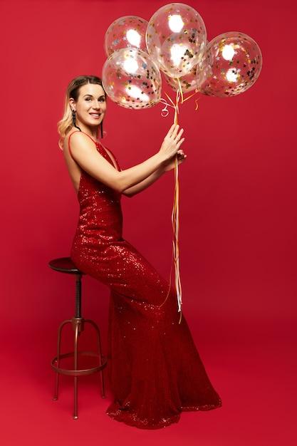 Belle Jeune Femme Chic Vêtue D'une Robe Rouge à Col Bas Posant Et Tenant Des Ballons Photo gratuit
