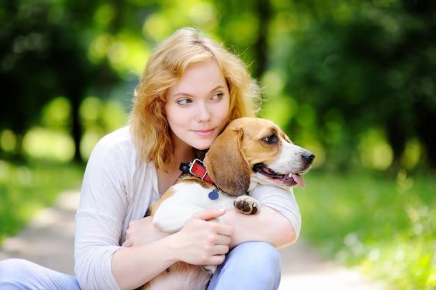 Belle jeune femme avec un chien beagle dans le parc de l'été. aimer propriétaire féminin avec son animal domestique Photo Premium