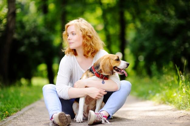 Belle jeune femme avec un chien beagle dans le parc de l'été Photo Premium