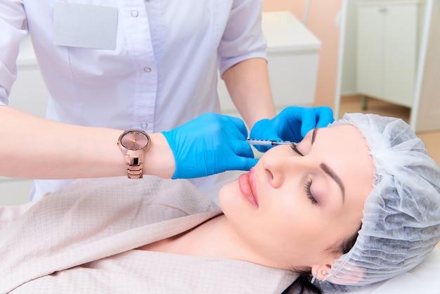 Belle jeune femme en clinique de cosmétologie esthétique. Photo Premium
