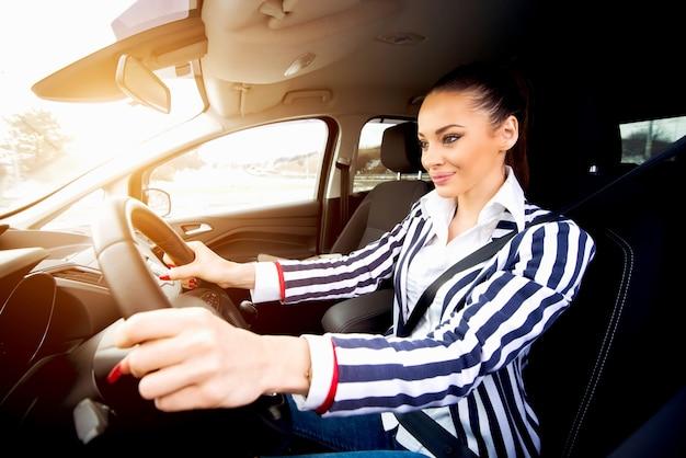 Belle Jeune Femme Conduisant Une Voiture En Souriant Et En Se Concentrant Sur La Balade. Photo Premium