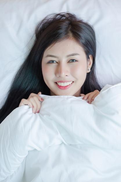 Belle jeune femme couchée dans le lit. Photo gratuit