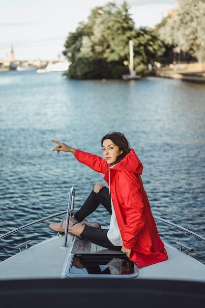Belle jeune femme dans un imperméable rouge monte un yacht privé. stockholm, suède Photo gratuit