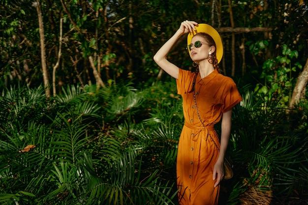 Belle Jeune Femme Dans La Jungle Tropicale Avec Chapeau Se Promène Dans Le Parc, Naturaliste Photo Premium