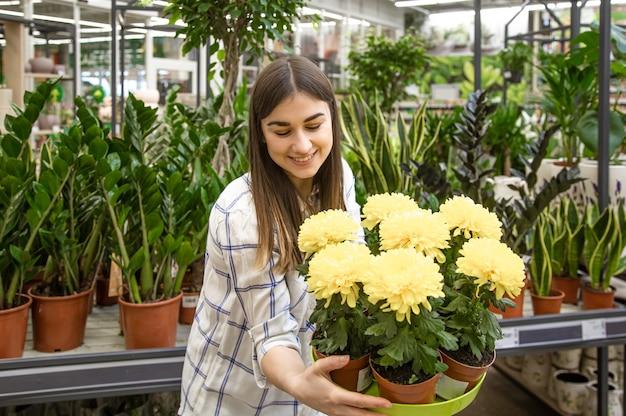 Belle Jeune Femme Dans Un Magasin De Fleurs Et Choisir Des Fleurs. Le Concept De Jardinage Et De Fleurs. Photo gratuit