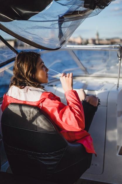 Belle jeune femme dans un manteau rouge, buvant du champagne sur un yacht. Photo gratuit