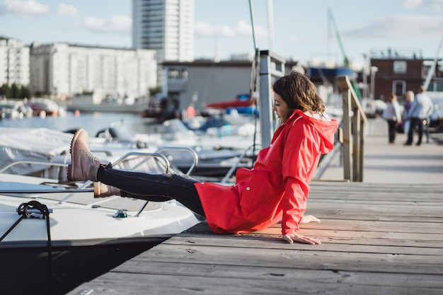Belle jeune femme dans un manteau rouge dans le port de yacht. stockholm, suède Photo gratuit