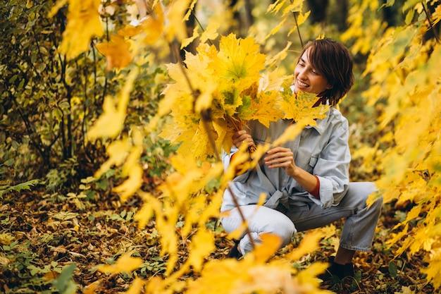 Belle jeune femme dans un parc d'automne rempli de feuilles Photo gratuit