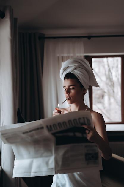 Belle Jeune Femme Dans Une Serviette Fume Une Cigarette Et Lit Le Journal Photo gratuit