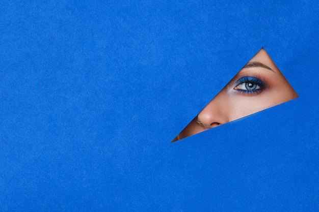 Belle jeune femme dans un trou de papier bleu, beau maquillage lumineux, Photo Premium