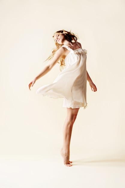 Belle jeune femme danse, fond clair studio. Photo Premium