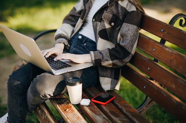 Belle Jeune Femme Debout Sur Un Banc à L'aide De L'ordinateur Portable Photo Premium