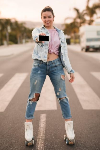 Belle jeune femme debout sur des patins à roulettes montrant un téléphone portable sur la route Photo gratuit