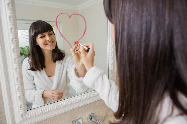 Belle jeune femme dessinant un grand coeur sur miroir avec rouge à lèvres Photo Premium