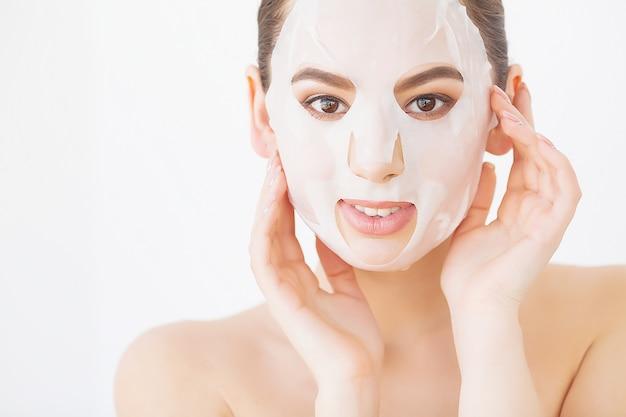 Belle jeune femme devient masque facial d'argile au spa, couché avec des concombres sur les yeux Photo Premium