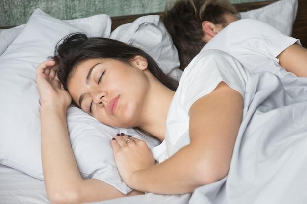 Belle jeune femme dort confortablement dans un lit confortable avec son petit ami Photo gratuit