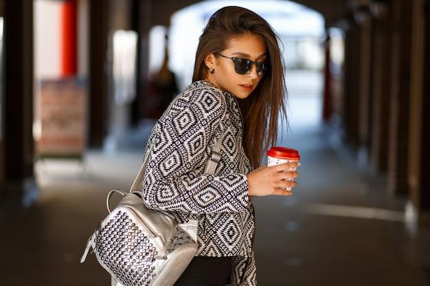 Belle Jeune Femme Avec Du Café Dans Des Vêtements à La Mode Avec Un Sac à Dos Marchant Dans La Ville Photo Premium