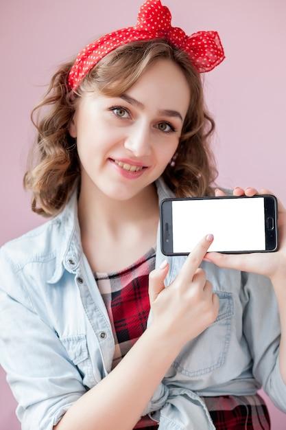Belle Jeune Femme Avec Du Maquillage Et Une Coiffure Pin-up Sur Fond Rose Avec Un Téléphone Mobile Avec Copie Espace Photo Premium