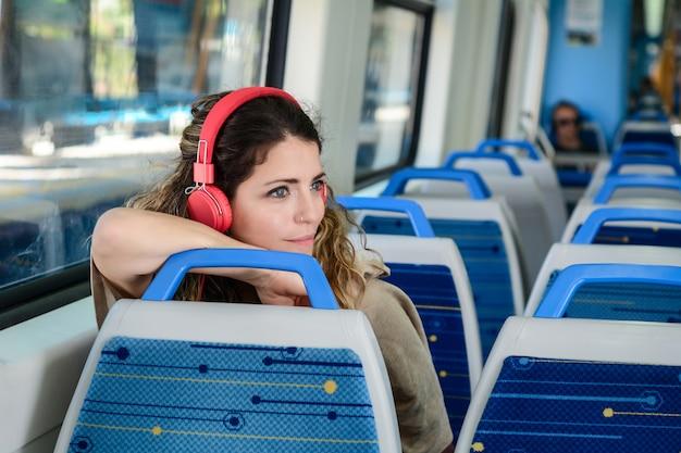 Belle jeune femme écoutant de la musique dans un train. Photo Premium