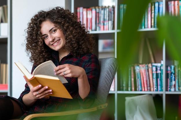Belle jeune femme est assise sur la chaise et feuilletant le livre en souriant joyeusement Photo Premium