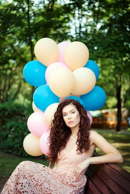 Belle Jeune Femme Est Assise Dans Le Parc Sur Un Banc Et Détient Des Ballons Multicolores Dans Les Mains Photo Premium