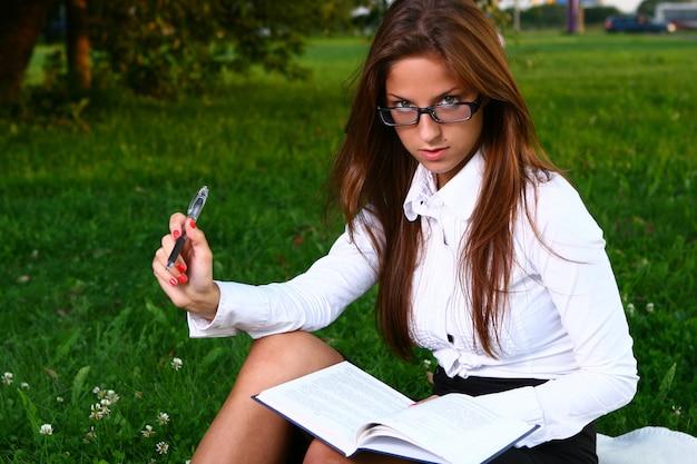 Belle jeune femme étudie dans le parc Photo gratuit