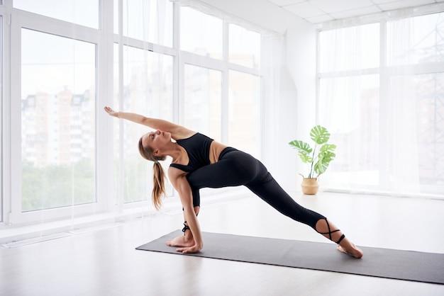 Belle Jeune Femme Faisant Du Yoga Dans Une Pièce Lumineuse Moderne Avec De Grandes Fenêtres. Yoga à La Maison. Photo Premium