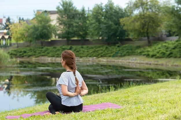 Belle Jeune Femme Faisant Des Exercices D'yoga Dans Le Parc Verdoyant Photo gratuit