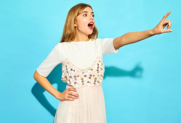 Belle Jeune Femme. Femme à La Mode Dans Des Vêtements D'été Décontractés. Modèle Féminin Positif Pointant Sur Les Ventes En Magasin Isolé Sur Mur Bleu Photo gratuit