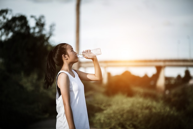 Belle jeune femme fitness boire de l'eau après l'exercice en cours d'exécution Photo gratuit