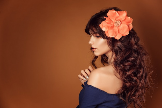 Belle jeune femme avec des fleurs dans les cheveux et le maquillage, photo tonique Photo Premium
