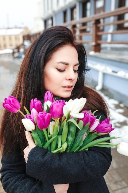 Belle Jeune Femme Avec Des Fleurs Portrait En Plein Air, Printemps Fille Tenir Bouquet Frais, élégante Dame à La Mode, Jolie Brune Beauté Féminine à La Rue De La Ville Photo Premium