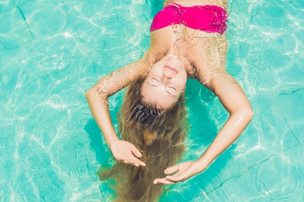 Belle Jeune Femme Flottant Dans La Piscine Vue De Dessus De Détente Photo Premium