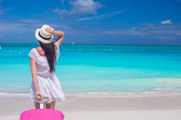 Belle jeune femme avec une grosse valise sur la plage tropicale Photo Premium