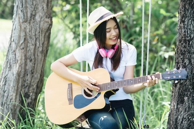 Belle jeune femme avec une guitare acoustique à la nature Photo gratuit
