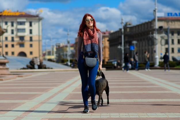 Belle Jeune Femme Heureuse Avec Mignon Chien Noir S'amuser Dans La Rue. Concept D'amitié Entre Les Animaux Et Les Humains. Photo Premium