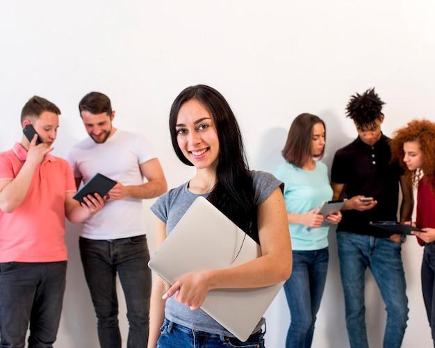 Belle jeune femme heureuse regardant la caméra tenant un ordinateur portable pendant que ses amis sont occupés à utiliser des gadgets électroniques Photo gratuit