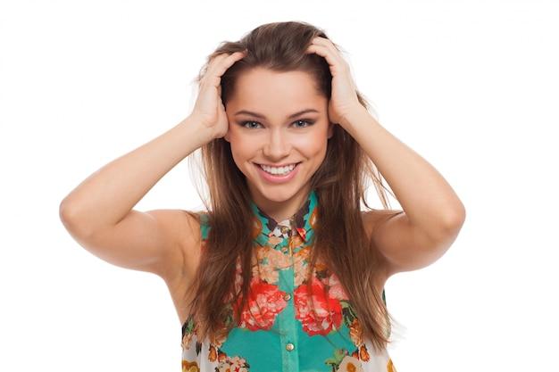 Belle jeune femme heureuse, tenant sa tête Photo gratuit