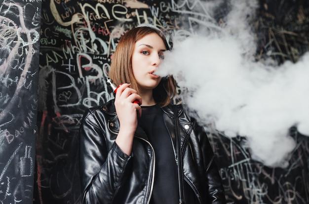 Belle jeune femme inhaler de la fumée. jeune fille vaping Photo gratuit