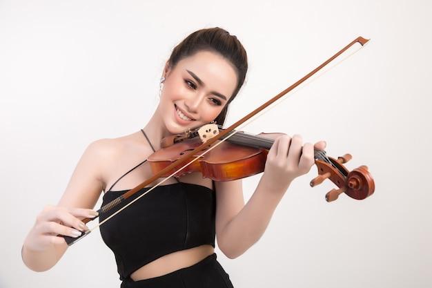 Belle jeune femme jouait du violon sur fond blanc Photo gratuit