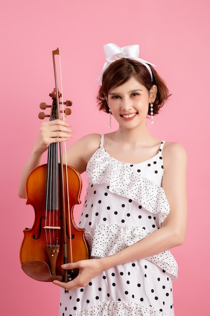 Belle jeune femme jouant du violon sur rose Photo gratuit