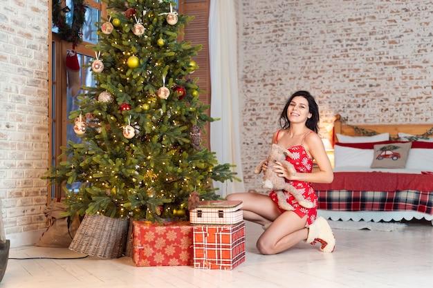 Belle Jeune Femme Jouant Avec Un Ours En Peluche Près De L'arbre De Noël Photo gratuit