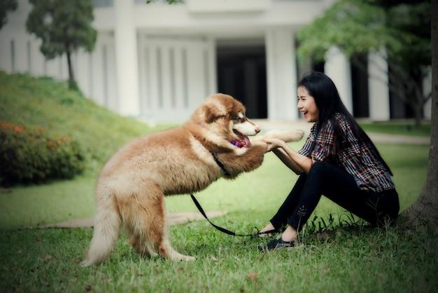 Belle jeune femme jouant avec son petit chien dans un parc en plein air. portrait de mode de vie. Photo gratuit