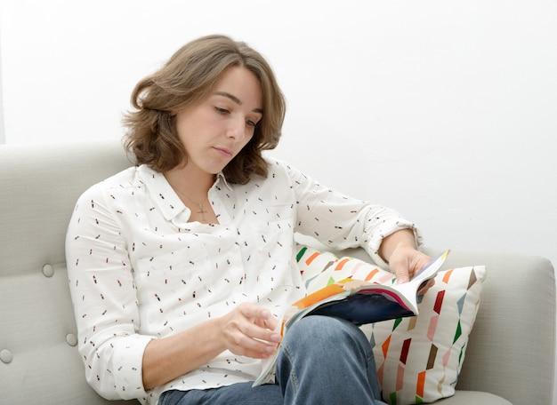 Belle jeune femme avec un livre dans le canapé Photo Premium